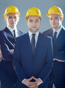 Serious young architects in suits and helmets looking at camera