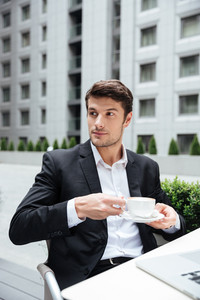 Serious young businessman drinking coffee in outdoor cafe