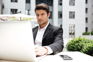 Serious young businessman sitting and using laptop in outdoor cafe