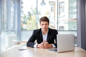 Serious young businessman with laptop sitting in office at the table