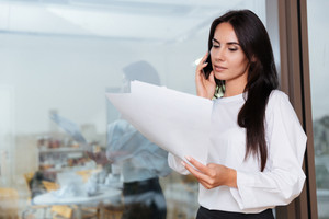 Serious young businesswoman working with documents and talking on mobile phone in office