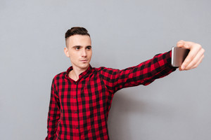 Serious young man in shirt making selfie in studio. Isolated gray background
