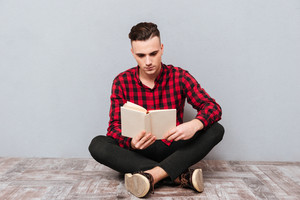 Serious young Man in shirt sitting on the floor and reading book. Isolated gray background