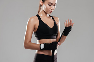 Serious Young Sporting woman in boxing bandages. Isolated gray background