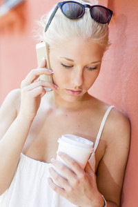 Serious young woman talking on the phone outdoors