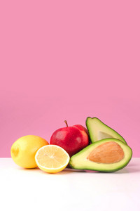 Set of fresh juicy lemon, apple, avocado isolated on pink background