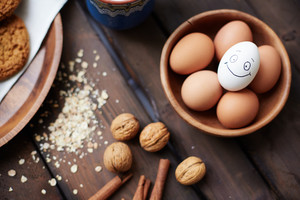Several eggs in bowl with walnuts and cinnamon near by