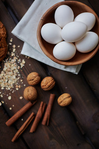 Several eggs in bowl with walnuts, flakes and cinnamon near by