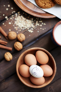 Several eggs in bowl with walnuts, milk and cinnamon near by