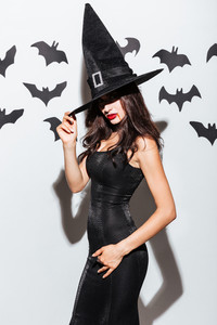 Sexy gothic young woman in black witch halloween costume with hat posing over white background