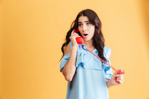 Shocked astonished beautiful woman in blue dress talking on red telephone isolated on a orange background