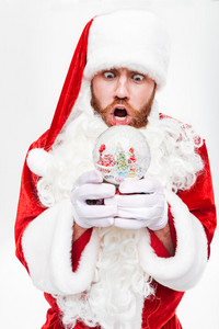 Shocked astonished man santa claus standing and holding snow ball