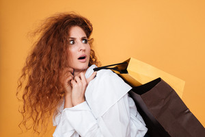Shocked astonished young woman holding shopping bags and talking on cell phone