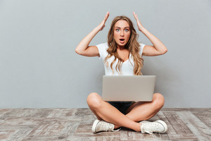 Shocked astonished young woman sitting with legs crossed and holding laptop over gray background
