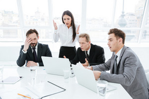 Shocked Business team by the table looking at laptop in conference room