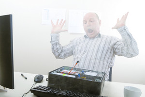 Shocked mature businessman with arms raised looking at smoke emerging from computer chassis in office