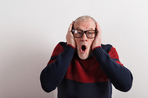 Shocked senior man in red and blue sweater and black eyeglasses holding head. Studio shot against white wall.
