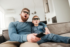 Shocked young father holding remote control while watching TV with his little cute son using 3d glasses.