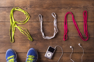 Shoelaces run sign, running shoes and mp3 player on a wooden floor background