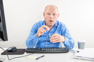 Sick and overworked office worker taking pill