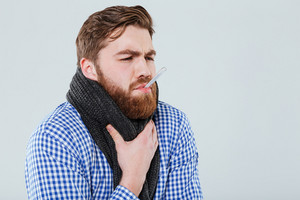 Sick bearded young man in scarf holding thermometer in his mouth measuring temperature