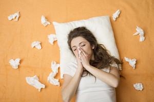 Sick woman lying in bed with cold and flu. She is blowing nose.