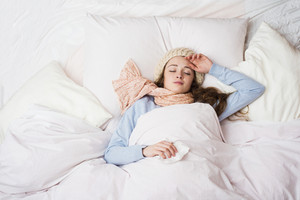 Sick woman lying in bed with high fever. She has cold and flu.