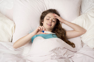 Sick woman with thermometer is lying in bed. She has cold, flu and high fever.