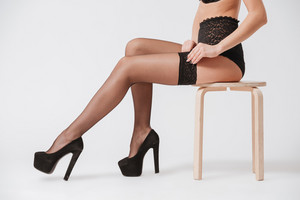 Side view close up of a young sexy woman in lingerie and stockings sitting on a chair isolated on a white background