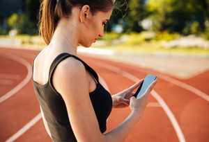 Side view of a beautiful woman resting after run and using smartphone on outdoor stadium