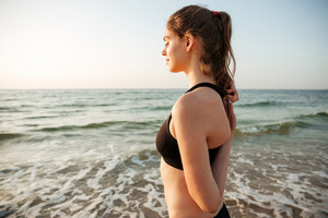 Side view of a beautiful young woman stretching hands during yoga on the beach