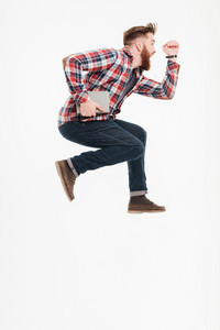 Side view of a casual bearded guy in plaid shirt jumping over white background