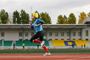 Side view of a fit young woman jogging at the stadium