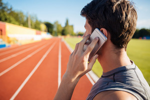 Side view of a male athlete standing on running track and talking on mobile phone