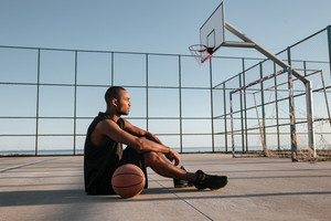 Side view of a tired young african sports man sitting with basketball at the playground