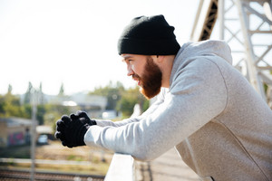 Side view of a young bearded sportsman in hat resting after workout while standing at the bridge
