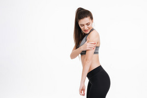 Side view of a young fitness woman in pain holding her arm and looking away isolated on a white background
