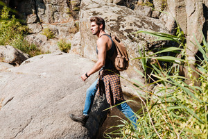 Side view of a young man exploring wilderness on trekking adventure