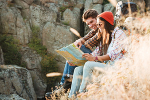 Side view of adventure couple with map sitting on slope. near the canyon