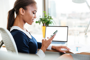 Side view of African business woman in dress sitting by the table near the window in office and looking at phone