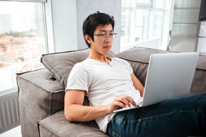 Side view of asian man with laptop on sofa. looking at laptop