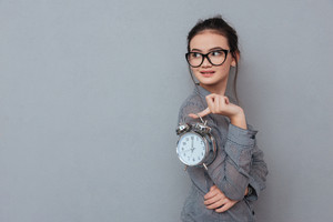 Side view of asian woman in glasses posing with clock and looking back. Isolated gray background