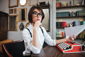 Side view of authoress in glasses and white shirt sitting by the table with paper and typewriter and looking at camera