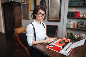Side view of Authoress in glasses and white shirt using typewriting and looking at camera