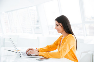 Side view of Business woman in orange shirt using laptop computer and sitting by the table in office