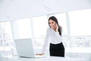 Side view of Business woman standing near the table, looking at laptop and talking at phone in office