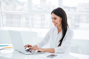 Side view of business woman using laptop and sitting by the table in office