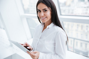 Side view of Business woman with tablet computer in hands standing near the window and looking at camera
