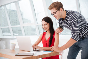 Side view of Couple by the table with laptop in office near the window. Man standing near woman which sitting on chair