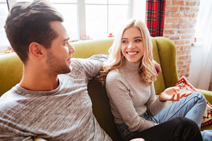 Side view of couple on sofa in home. looking into each other's eyes